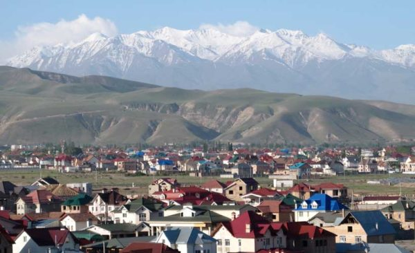 Kyrgyzstan Village with snow capped mountains in the background