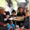 Kyrgyzstan-family-in-wooden-hut-eating-meal