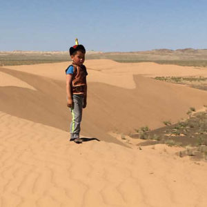 Little boy in nomadic outfit on the dunes in Mongolia