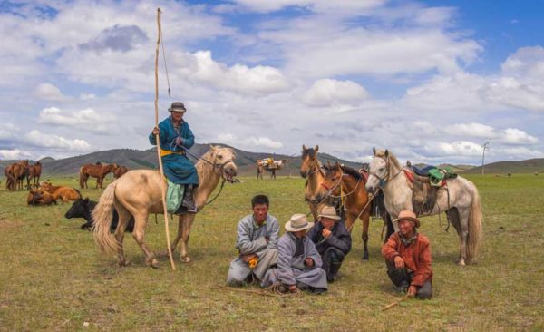 Small group of Mongolian horsemen and their horses