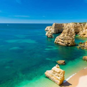 Blue green water and dramatic cliffs of the Algarve Portugal