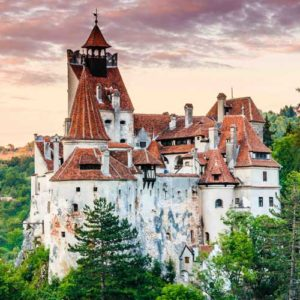 Bran or Dracula's castle perched on a hill surrounded by trees