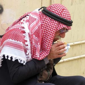 Visit Israel - Palestinian man with red and white head shawl eating his lunch